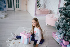 Girl sitting with gift boxes near Christmas tree at home Royalty Free Stock Image