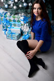 Girl sitting with gifts under the Christmas tree Royalty Free Stock Images