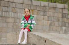 Girl sitting a granite embankment on ramp Stock Image