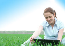 Girl sitting in the grass. With laptop Stock Image