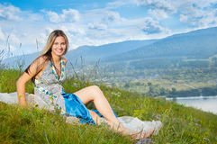 Girl sitting on grass Stock Images