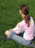 Girl sitting on grass. Girl sitting on green grass royalty free stock images