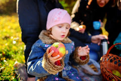 Girl sitting on the grass with an apple in his hand Stock Images