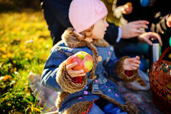 Girl sitting on the grass with an apple in his hand. Early autumn Royalty Free Stock Photography