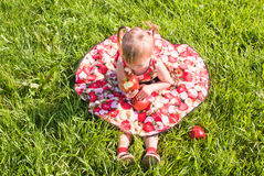 Girl sitting on the grass with apples Royalty Free Stock Images