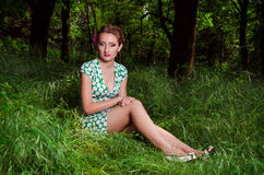 Girl sitting on the grass. Beautiful girl sitting on the grass in the park royalty free stock photos