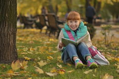Girl sitting on grass  book with a book, funny expression on his face Royalty Free Stock Photos