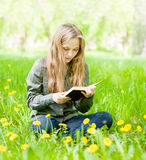 Girl sitting on grass with dandelions and reading a book Stock Photos