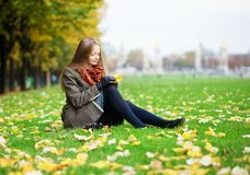 Girl sitting on a grass on a fall day Stock Photo