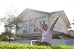 Girl sitting on grass field with modern home background Royalty Free Stock Photos