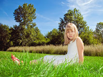 Girl sitting on grass Stock Image