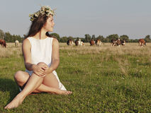 Girl sitting on grass meadows Stock Images
