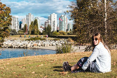 Girl Sitting on the Grass near Vanier Park in Vancouver, Canada Stock Image