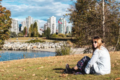 Girl Sitting on the Grass near Vanier Park in Vancouver, Canada Stock Images