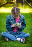 Girl sitting on grass at park and exploring globe Royalty Free Stock Photography