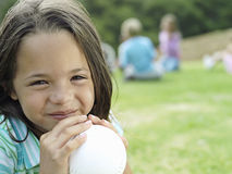 Girl (7-9) sitting on grass in park, holding ball, smiling, portrait, focus on foreground stock photos