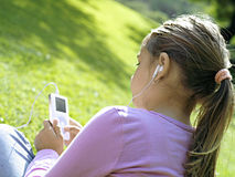 Girl (7-9) sitting on grass in park, listening to MP3 player, rear view, close-up (tilt) Stock Images
