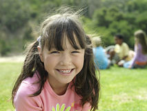 Girl (7-9) sitting on grass in park, smiling, portrait, focus on foreground royalty free stock image