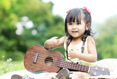 Girl sitting on grass and play ukulele in garden Royalty Free Stock Photos