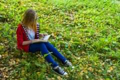 Girl sitting on grass and reading a book. Girl teenager in red jacket sitting on grass a book Royalty Free Stock Photo