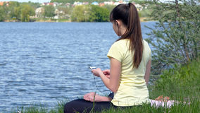 Girl sitting on the grass and relaxing meditating. Young woman meditating and listening music on smartphone in headphones in lotus position. Girl sitting on the Royalty Free Stock Image