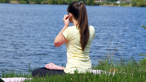 Girl sitting on the grass and relaxing meditating. Young woman putting earphones in her ears and meditating in lotus position. Girl sitting on the grass and Stock Photography