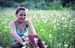 Girl sitting in grass smiling. Smiling young woman sitting alone in an overgrown meadow Stock Image