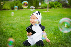 Girl sitting on grass with soap bubbles Stock Photo