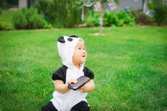 Girl sitting on grass with soap bubbles Stock Photography