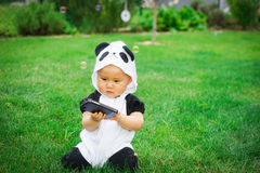 Girl sitting on grass with soap bubbles. Baby girl asian dressed as panda sitting on the green grass outdoor playing with soap bubbles Royalty Free Stock Photography
