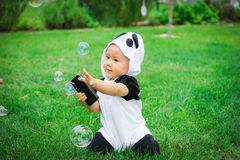 Girl sitting on grass with soap bubbles Stock Image