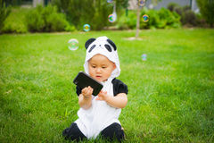 Girl sitting on grass with soap bubbles Royalty Free Stock Photo