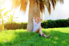 Girl sitting on the grass under a palm tree Royalty Free Stock Images