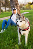 Girl sitting in the grass after walking with her pet husky dog Royalty Free Stock Images