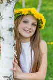 Girl are sitting in the grass with wreath of dandelions on her h Stock Photos