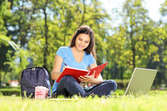 Girl sitting on grass and writing in a notebook Stock Photography