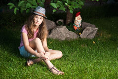 Girl sitting on grassy meadow next to a tree and G Stock Image