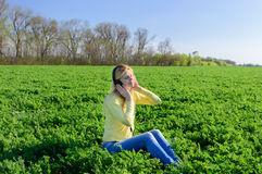 Girl sitting on a green field Stock Image