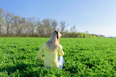 Girl sitting on a green field Royalty Free Stock Images