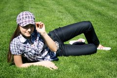 Girl sitting on the green grass Stock Photos