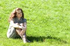 Girl sitting on green grass Royalty Free Stock Photography
