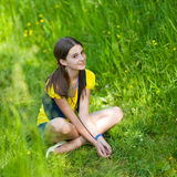 A girl sitting on green grass Stock Images