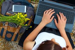 Girl sitting on green grass with laptop hands on keyboard stock images