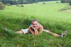 Girl sitting in green grass in the meadow Stock Photos