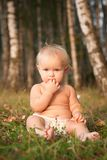Girl sitting on green grass near forest Royalty Free Stock Images
