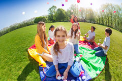 Girl sitting on green lawn holding colorful balls. Fish eye picture of laughing girl sitting on rainbow parachute and holding colorful balls in her hands stock images
