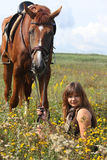 Girl sitting on the ground and chestnut horse standing near Royalty Free Stock Photography
