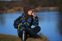 Girl sitting on the ground and drink tea after hike Stock Photography