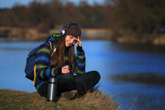 Girl sitting on the ground and drink tea after hike Stock Images