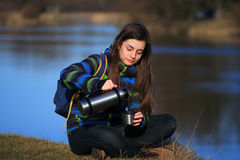 Girl sitting on the ground and drink tea after hike Stock Photos